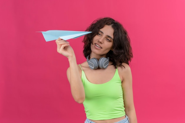 Uma jovem mulher atraente com cabelo curto em um top verde recortado em fones de ouvido olhando para um avião de papel azul