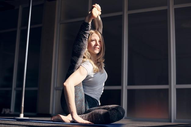 Uma jovem mulher atraente, com cabelos claros pratica ioga. yoga, fitness, estilo de vida saudável