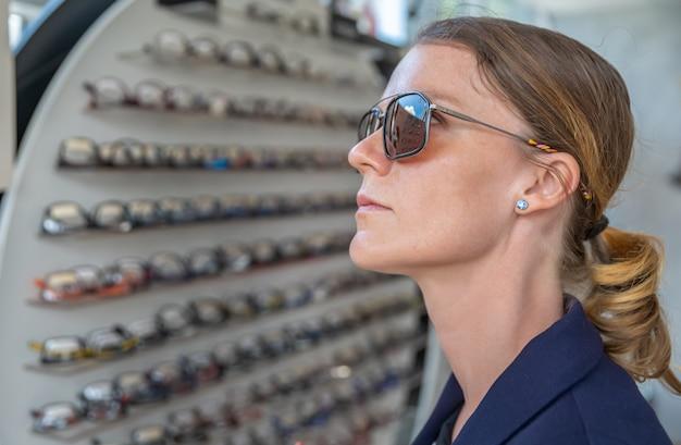 Uma jovem mulher atraente em uma loja de óptica experimenta novos óculos