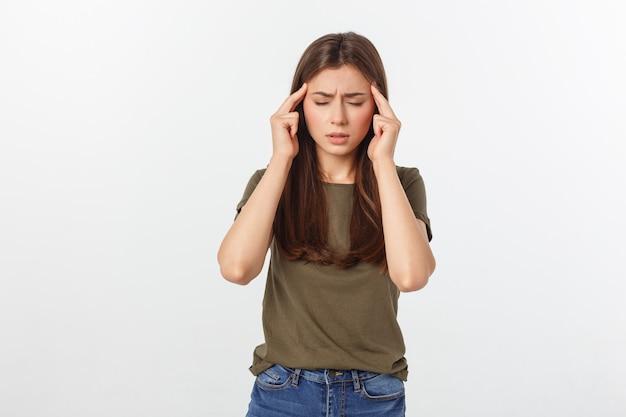 Uma jovem mulher atraente, sofrendo de doença ou dor de cabeça, segurando sua cabeça. isolado no branco