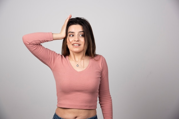 Uma jovem mulher atraente vestida com roupas casuais, segurando a palma da mão levantada na cabeça.