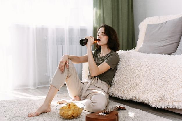 Uma jovem mulher bebe cerveja e come batatas fritas em casa