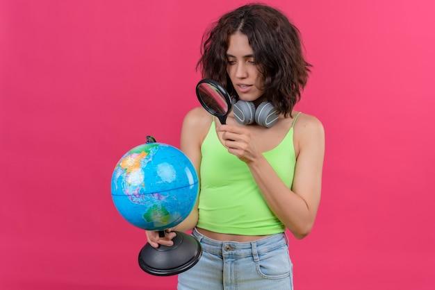 Uma jovem mulher bonita com cabelo curto em um top verde recortado em fones de ouvido olhando para o globo com uma lupa