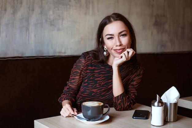 Uma jovem mulher bonita com cabelo escuro de aparência caucasiana com maquiagem em um vestido marrom está sentada ...