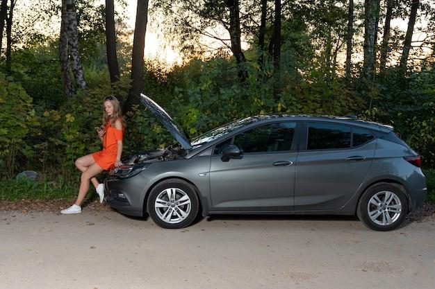 Uma jovem mulher bonita com um carro quebrado, usando telefone celular para chamar assistência na estrada