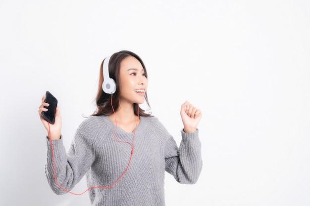 Uma jovem mulher bonita com um suéter cinza está mentindo e ouvindo música usando fones de ouvido brancos.