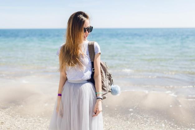 Uma jovem mulher bonita com uma camiseta cinza e uma saia exuberante está de pé perto do mar