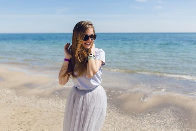 Uma jovem mulher bonita com uma saia cinza exuberante e uma camiseta está em pé perto do mar