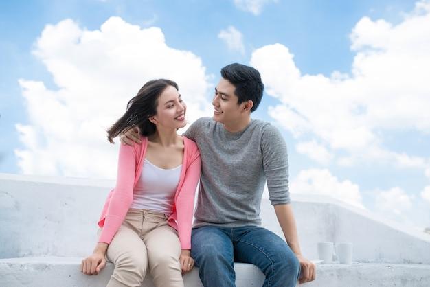 Uma jovem mulher bonita e um homem asiático riem contra o céu azul escuro com nuvens