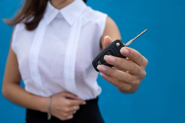 Uma jovem mulher bonita em um pano de negócios segurando a chave do carro na parede azul