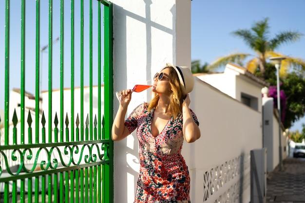Uma jovem mulher bonita em um vestido curto caminha pelas ruas de uma pequena cidade europeia.