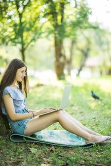 Uma jovem mulher bonita está sentada na grama verde sob a árvore no jardim num dia de verão e trabalhando em seu laptop