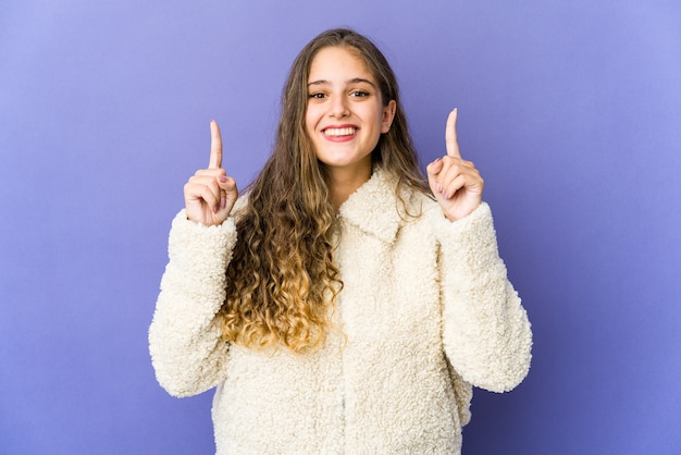 Uma jovem mulher bonita indica com os dois dedos indicadores para cima, mostrando um espaço em branco
