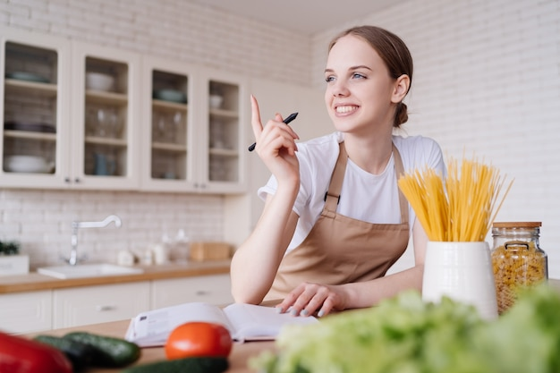 Uma jovem mulher bonita na cozinha, de avental, escreve suas receitas favoritas ao lado de legumes frescos