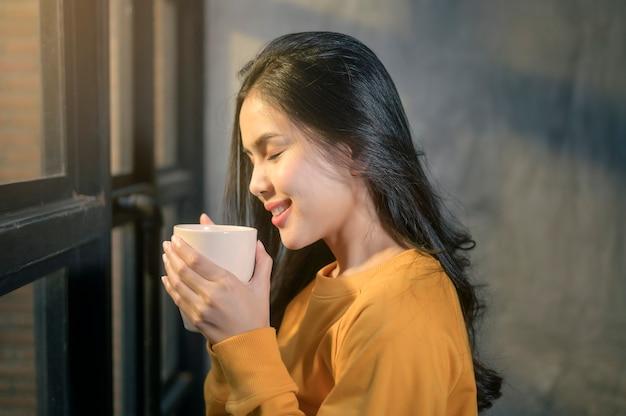 Uma jovem mulher bonita na luz do sol, apreciando seu café da manhã em casa