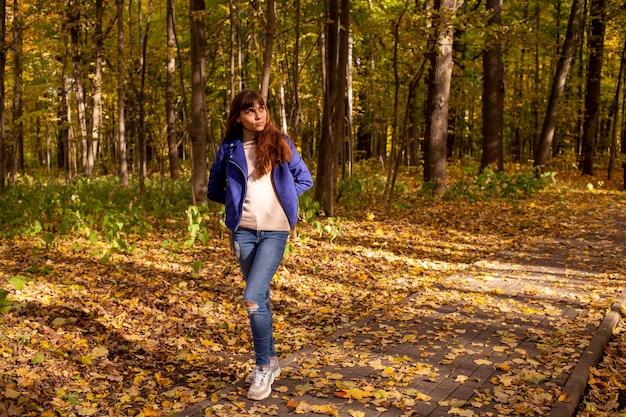 Uma jovem mulher bonita no parque de outono e o sol brilha no fundo das árvores amarelas