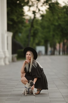 Uma jovem mulher bonita no verão curto vestido posando em uma rua da cidade com seu cão pequeno espanador bonito.