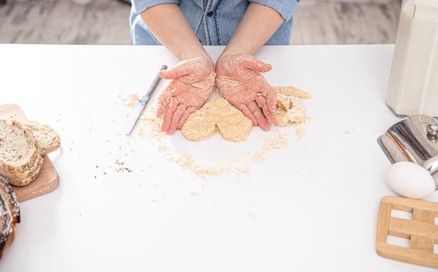 Uma jovem mulher bonita prepara bolos caseiros na cozinha