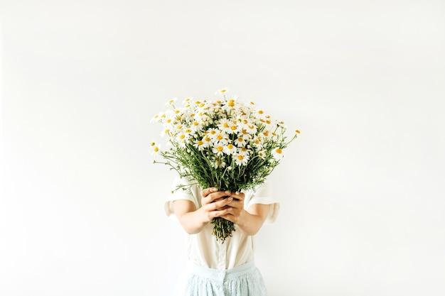 Uma jovem mulher bonita segurando um buquê de flores de margarida de camomila branca na superfície branca