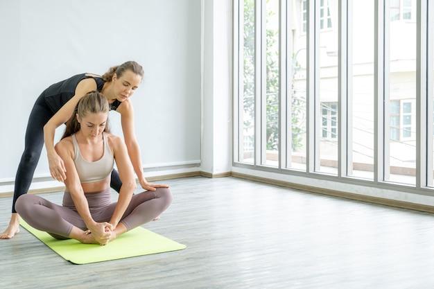 Uma jovem mulher caucasiana está ensinando ioga pose de alongamento para uma amiga em casa.