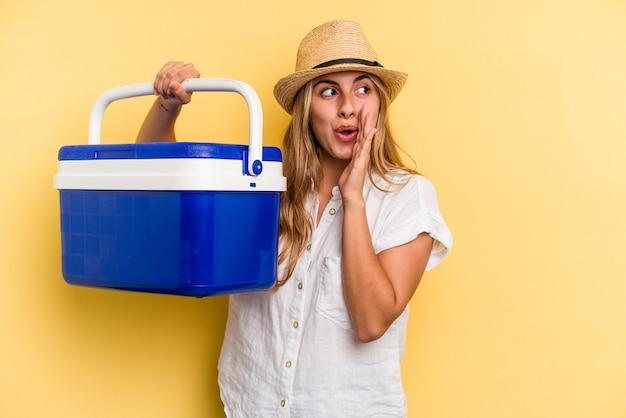 Uma jovem mulher caucasiana segurando uma geladeira isolada em um fundo amarelo está contando uma notícia secreta de travagem e olhando para o lado