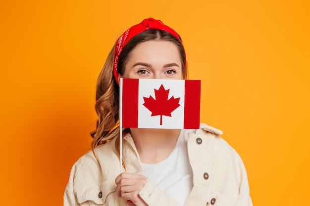 Uma jovem mulher cobre o rosto com uma pequena bandeira do canadá