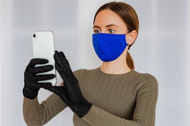 Uma jovem mulher com cabelo castanho claro, segurando um smartphone branco nas mãos em luvas de látex médicas pretas, vestindo uma máscara facial médica de algodão azul