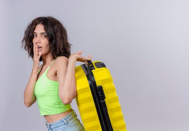 Uma jovem mulher com cabelo curto, com top verde cortado, mantendo a mão na boca e segurando uma mala amarela sobre um fundo branco