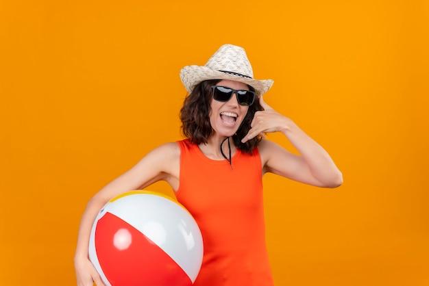 Uma jovem mulher com cabelo curto e uma camisa laranja usando chapéu de sol e óculos escuros segurando uma bola inflável e mostrando o gesto de me ligar