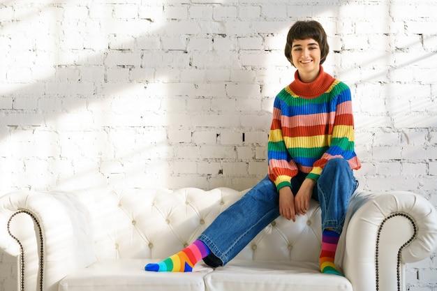 Uma jovem mulher com cabelo curto em um suéter arco-íris e meias está sentada em um sofá branco