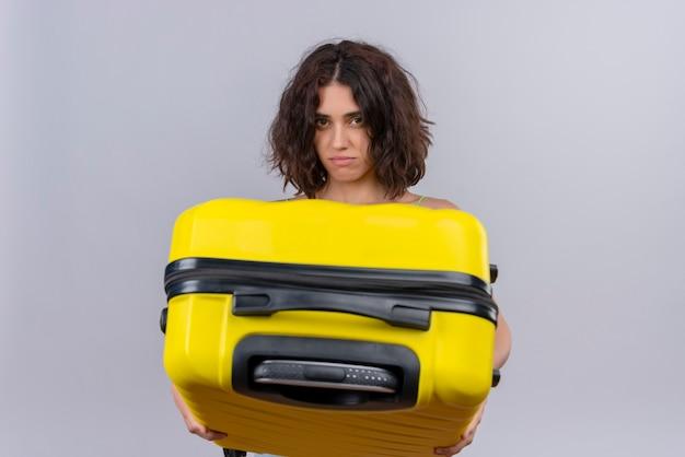 Uma jovem mulher com cabelo curto em um top verde cortado segurando uma mala amarela sobre um fundo branco