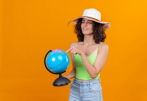 Uma jovem mulher com cabelo curto, usando uma blusa verde e chapéu de sol apontando para um globo com o dedo indicador