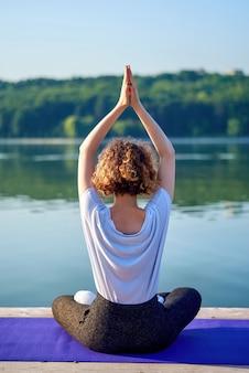 Uma jovem mulher com cabelos cacheados, fazendo yoga fora