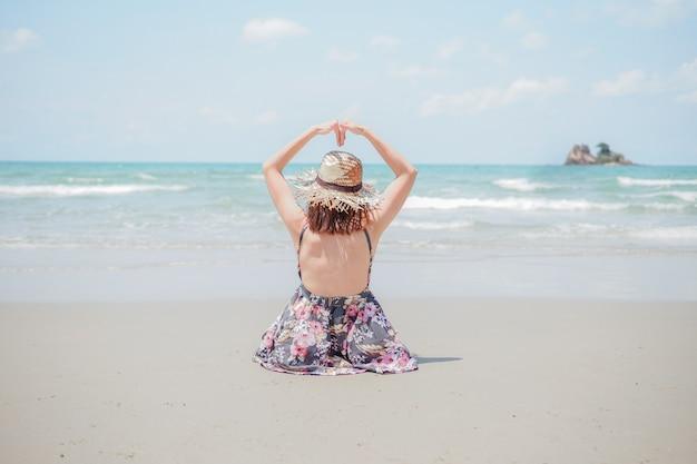 Uma jovem mulher com chapéu está sentado na praia