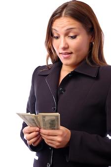 Uma jovem mulher com dólares nas mãos dela, isolados