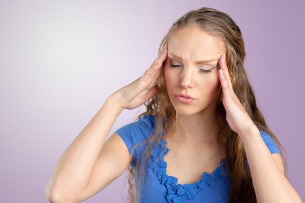 Uma jovem mulher com dor de cabeça, segurando a cabeça