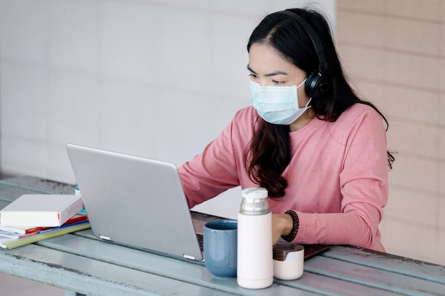 Uma jovem mulher com máscara facial trabalhando em um laptop em casa durante a pandemia de coronavirus ou covid-19 .. um aluno ault estudando online em casa. foto