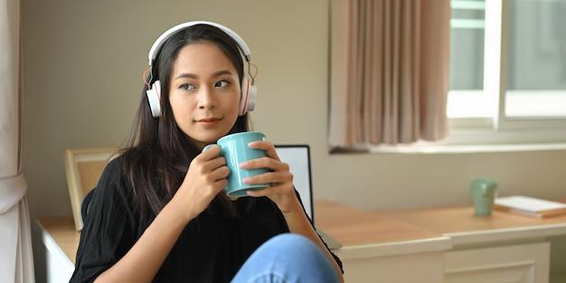 Uma jovem mulher com o fone de ouvido está segurando uma xícara de café enquanto está sentado e ouvindo música.