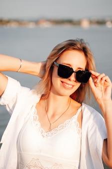 Uma jovem mulher com óculos de sol ao amanhecer, retrato de uma bela jovem loira em um vestido branco e uma camisa.