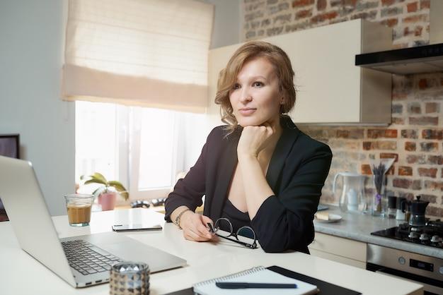 Uma jovem mulher com óculos trabalha remotamente em um laptop em sua cozinha. uma loira ouvindo seus colegas em uma videoconferência em casa. uma senhora séria estudando uma lição on-line em um webinar.