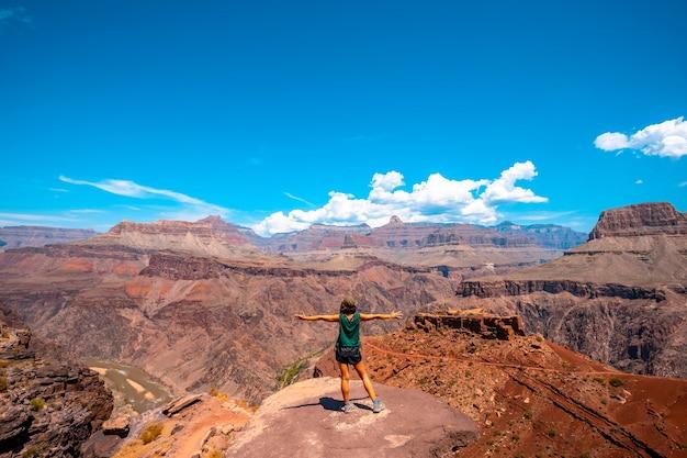 Uma jovem mulher com os braços abertos em um ponto de vista da caminhada na trilha south kaibab. grand canyon
