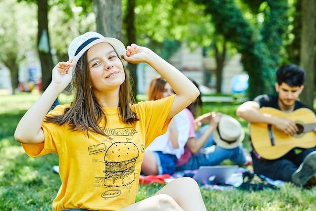 Uma jovem mulher com seus amigos se divertindo no parque, sentada na grama