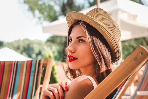 Uma jovem mulher com um chapéu de palha com batom vermelho se senta em uma cadeira de praia