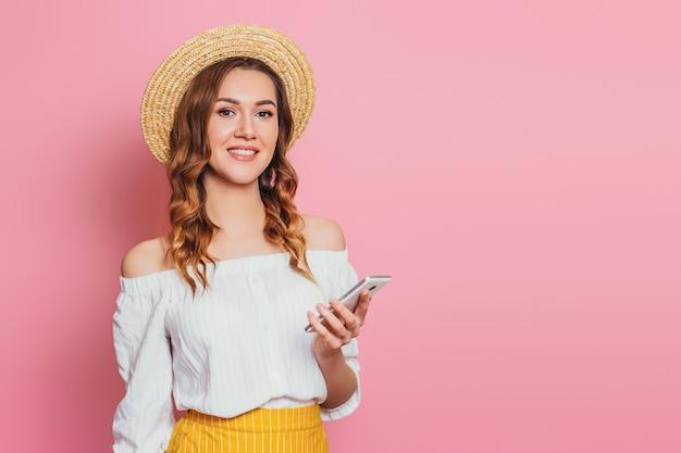 Uma jovem mulher com um chapéu de palha e um vestido de verão branco com um telefone móvel, sorrindo em um banner de parede rosa web. garota faz compras on-line e mantém o smartphone no espaço vazio de mão