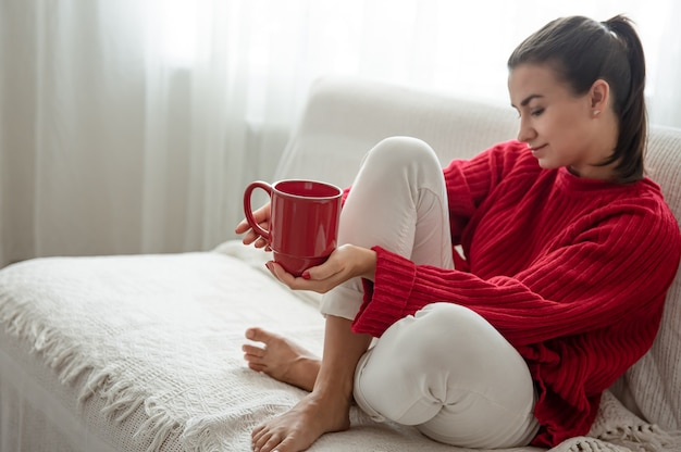Uma jovem mulher com um copo vermelho de bebida quente em um suéter vermelho aconchegante está descansando no sofá em casa, copie o espaço.