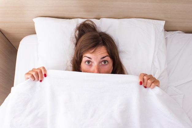 Uma jovem mulher com um rosto surpreso está deitada na cama. insônia de conceito, sonhos, pílulas para dormir, bom sono, bom sexo. vista plana, vista superior