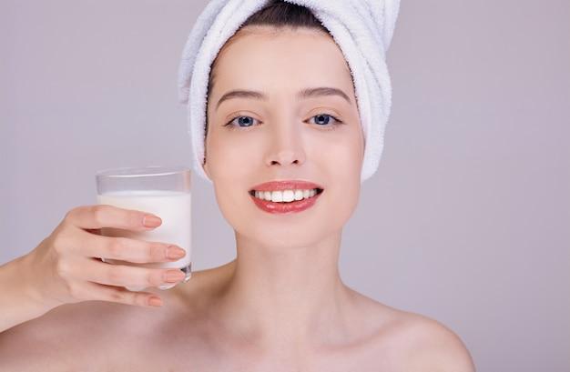 Uma jovem mulher com um sorriso largo segura um copo com leite.