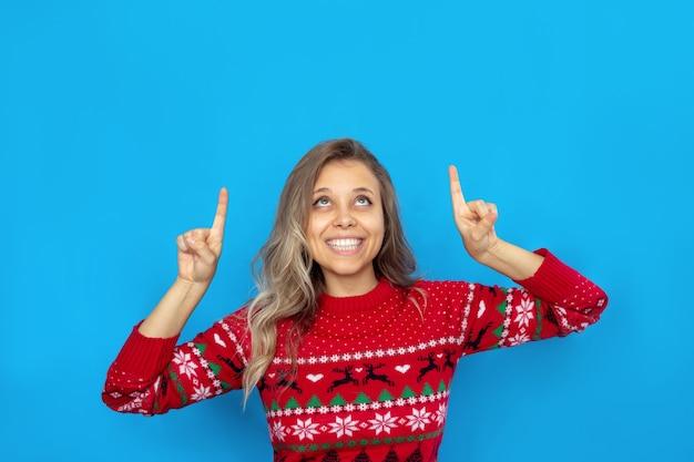 Uma jovem mulher com um suéter vermelho de natal com veados aponta para o espaço vazio da cópia para o texto de saudação
