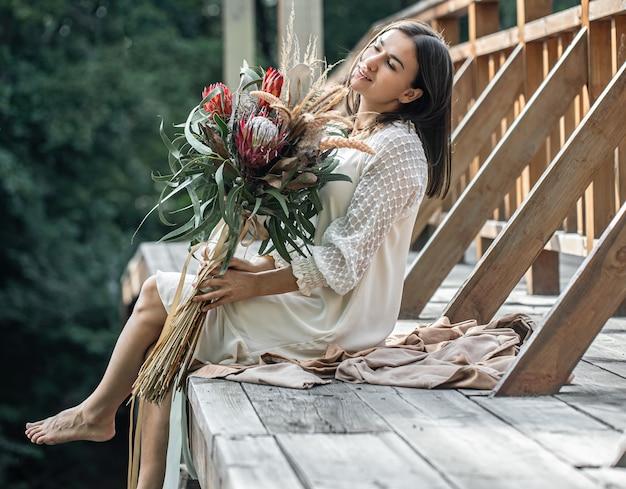 Uma jovem mulher com um vestido branco está sentada em uma ponte de madeira com um buquê de flores exóticas.