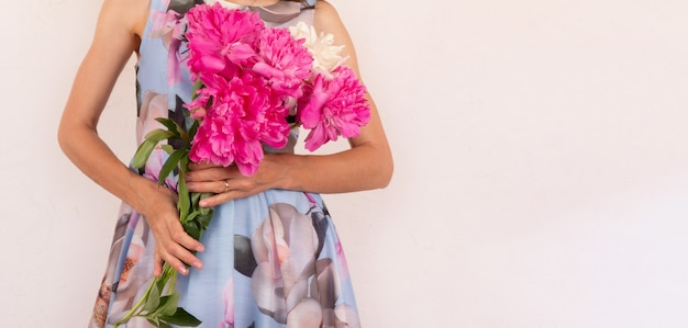 Uma jovem mulher com um vestido colorido com um buquê de flores de peônia nas mãos em um fundo rosa claro com um espaço de cópia